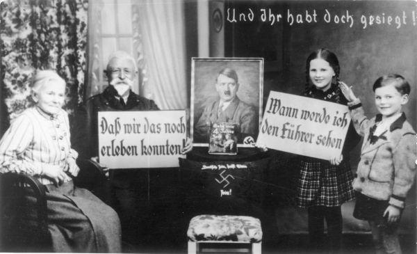 Großeltern und Enkel beim Posieren mit Propagandaschildern