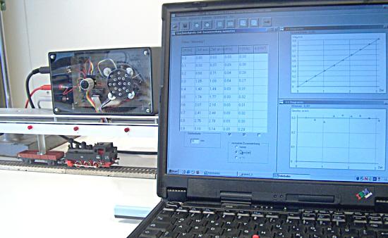 Ausschnitt aus dem Aufbau: Bahn, Lichtschrankenschiene und Laptop