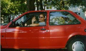 Jugendlicher winkt aus Kleinwagen